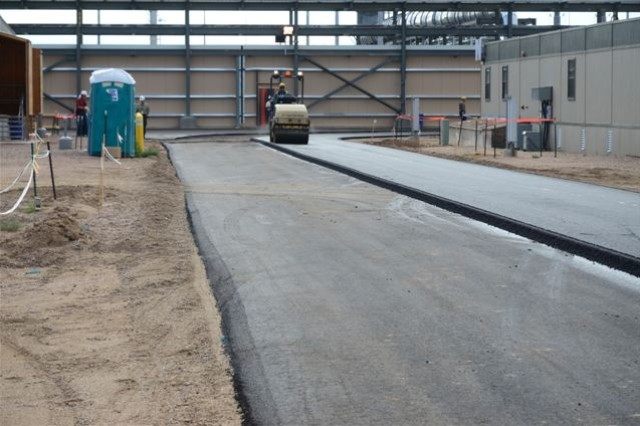 On the west side of the Automated Guided Vehicle Corridor, workers are busy paving roadways.