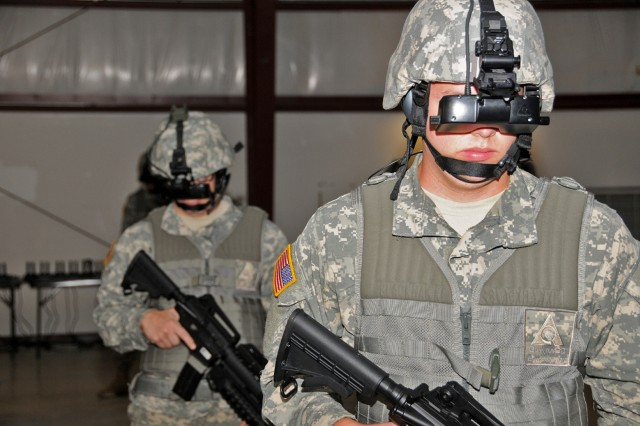 Pfc. Kevin Hadley, a forward observer with the 151st trains with a human immersion combat simulator at Camp Atterbury Joint Maneuver Training Center Sept. 12. The system uses goggles and various other sensors worn by Soldiers to put them in a virtual simulation of a combat zone. The training was part of a training exercise called Bold Quest 2011, a joint staff led combat coalition exercise to test the interoperability of target identification systems of member nations to reduce friendly fire incidents.