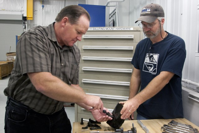 PICATINNY ARSENAL, N.J. - Ron Hoehn (left) replaces a firing pin for an Mk11 Saluting cannon while Rich Moore braces the breechblock. Hoehn and Moore, gun systems technicians from Naval Surface Warfare Center, Indian Head Division's Picatinny Detachment, made an early five-hour drive on Sept. 16 to Washington, D.C. to repair a Mk11 cannon that was used during a ceremony at Marine Corps Barracks honoring Sgt. Dakota Meyer. Meyer earned the Medal of Honor for heroic actions on Sept. 8, 2009, near the village of Ganjgal, Afghanistan.