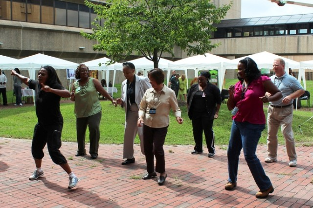 Fitness Center manager Nadine Lilavois leads a group of ALC workers in a Latin dance demonstration during the 2011 Health, Wellness and Resiliency Expo at the Adelphi Lab Center.