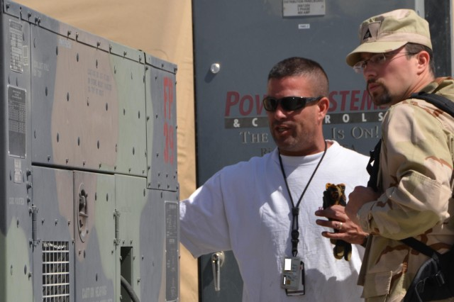 Joe Barniak, contractor with Project Manger-Mobile Electric Power, and Michael J. Zalewski, RFAST-C mechanical engineer, stand in front of a power panel while looking at a Tactical Quiet Generator at Camp Sabalu-Harrison. The power panel is part of the Afghan Microgrid Project that provides power to more than 60 structures at the camp with greater efficiency than the 20 plus TQGs it replaces.