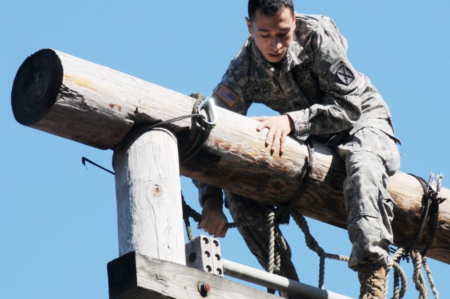 "A Soldier climbs over an obstacle during ""zero day."""