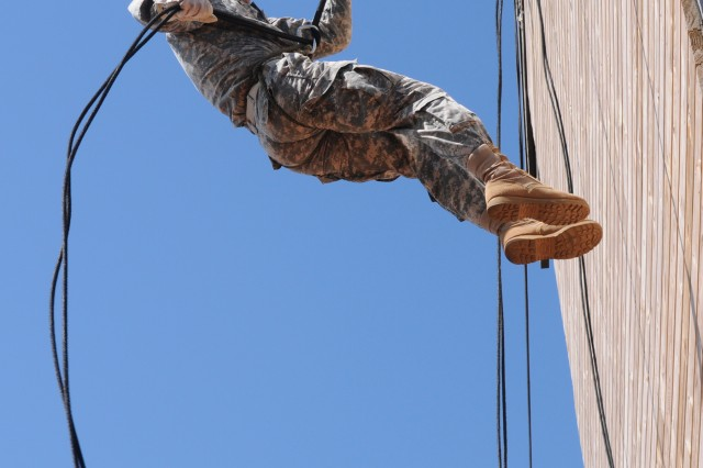 A soldier repels down a 45-foot tower during Air Assult School training.