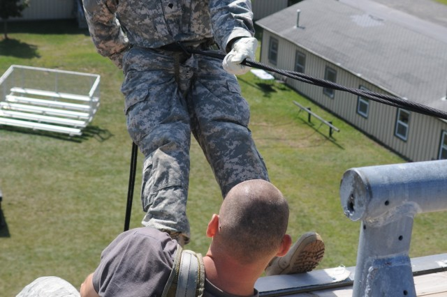 Spc. Ian Stavola, 10th Brigade Support Battalion, listens to his instructions before rappelling off a 45-foot tower.