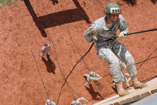 Spc. Trey Foster, 1st Brigade Combat Team, smiles while he rappels down a 45-foot tower during Air Assault School last month. Foster and 111 others earned the coveted badge.