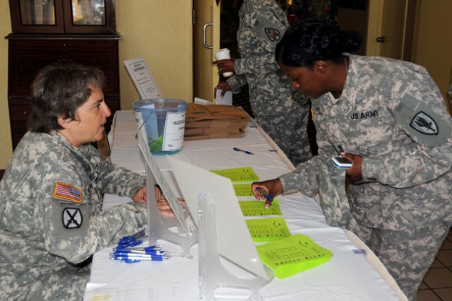 Staff Sgt. Marci Nemtzow, left, a CFC volunteer, greets a fellow Soldier and explains the agency's bingo game at the CFC kickoff event at the Landing Sept. 21.