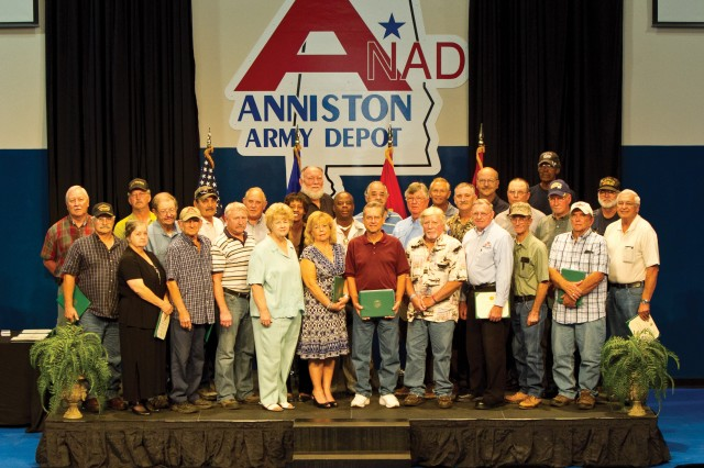 On Sept. 27, at Anniston Army Depot's Consolidated Retirement Ceremony, retirees pose for a group photograph.  They are: Melissa D. Baldwin, William D. Butler, Kenneth F. Butterworth, Nora Callahan, Patricia M. Chupp, Michael P. Cofield, Sallie B. Curry, Roger D. Dunaway, Thomas R. Hebbard, Kenneth G. Higgins, Lorenza Johnson, Randy L. Jones, Max W. King, Charles M. Lackey, Lanny D. Lankford, Ricky L. McComb, Radford O. McCurdy, Ernest M. McCurry Jr., Johnnie Moore, Homer E. Parton, John Patterson, Kenneth P. Pitts, Harold W. Presson, John C. Proctor, Robert M. Skidmore, Ronnie G. Thompson, James S. Turner, Ralph Usrey and Thomas D. Vaughan Jr. Not pictured were Orbia Hester, Willie J. Lee, Ernest E. Rodriguez and David Williams Jr.  A collective 1,045 years of service was officially recognized.