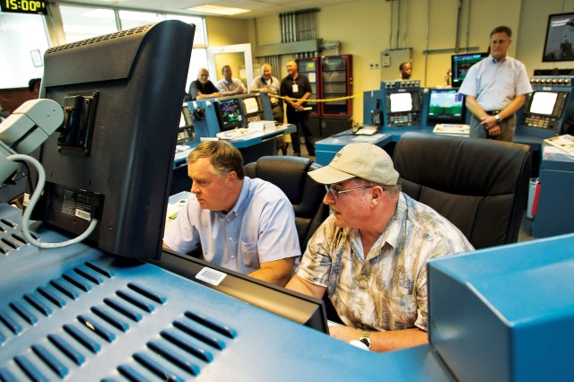 Ted Gerth, a Westinghouse Anniston control room operator, guides Timothy K. Garrett, government site project manager at the Anniston Chemical Agent Disposal Facility, as he uses a computer to move destroyed chemical munitions out of the facility's metal parts furnace Sept. 22, 2011.