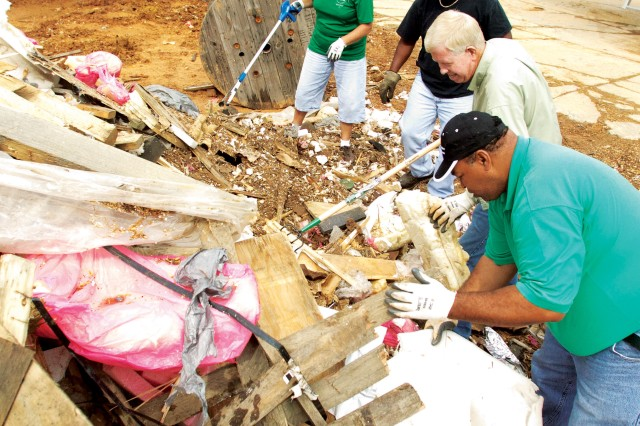 Teresa Turner, Kendal Powell, Richard Brimer and Earl Montgomery of Anniston Army Depot remove recyclable material from a pile of waste at the wood yard Sept. 27.