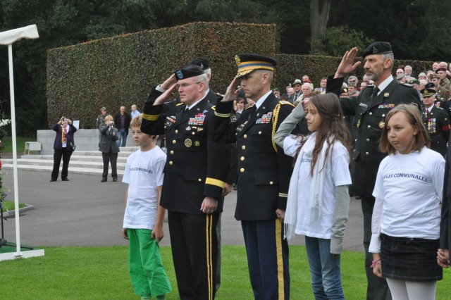 V Corps Acting Commanding General, Brig. Gen. Ricky Gibbs, left, is flanked by Belgian schoolchildren as he salutes to honor the memory of U.S. World War II veterans who gave their lives in the campaign that liberated France and Belgium, at Ardennes American Cemetery near Liege, Belgium, Sept. 22. Col. Brendan B. McAloon, center, Defense Attache at the U.S. Embassy in Belgium, joins Gibbs.
