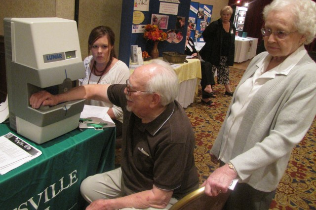 Military retiree Robert Duncan takes a bone density test at the 2010 Retiree Appreciation Day health fair last Oct. 1 in the Officers and Civilians Club. Administering the test is Brook Berg. Duncan's wife, Faye, stands behind her husband.