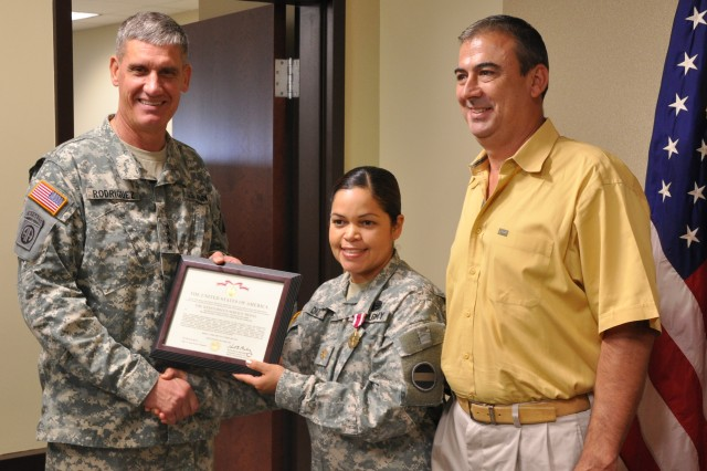 FORT BRAGG, N.C. (Sept. 29, 2011)- Gen. David M. Rodriguez, Commanding General, U.S. Army Forces Command (FORSCOM), congratulates Maj. Ellen Diaz-O'Neill and her husband Michael O'Neill in a ceremony here today by presenting her certificate for the Meritorious Service Medal.  Diaz-O'Neill earned the medal for her distinguished performance of duty while serving as the FORSCOM G4 Logistics, Plans and Operations Officer.  (Photo by Bob Harrison, FORSCOM Public Affairs)
