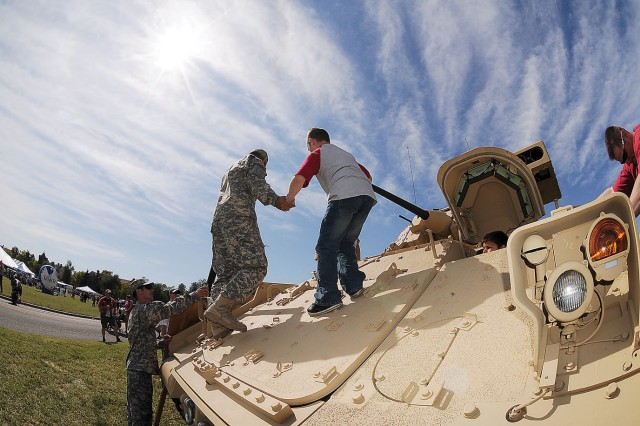 Pfc. James Nelson, 2nd Bn, 34th Armor Regt.,  1st HBCT, 1st Inf. Div., assists Blake Hull, 9,  as he exits a M2A2 infantry fighting vehicle on display at Fort Riley's Fall Apple Day Festival Sept. 24 at Artillery Parade Field, Fort Riley, Kan.