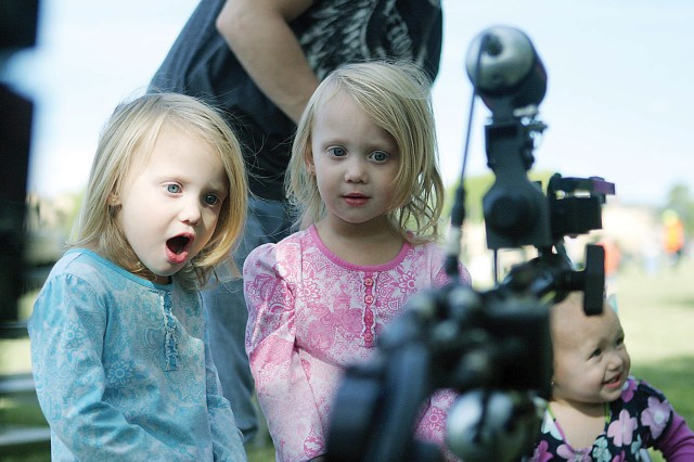 Anna and Allison McDowell, 3-year-old twins, react while watching a bomb disposal robot perform a demonstration at the EOD display during Fall Apple Day Festival Sept. 24 at Artillery Parade Field, Fort Riley, Kan.
