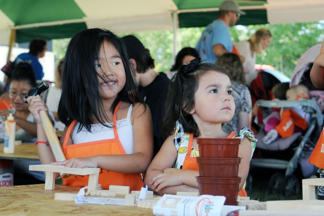 Kayla Wisdom, 5, left, and Emmalie Venegas, 3, left, listen to instructions on how to build their project from Emmalie's mother, Nicole Venegas, at the Home Depot tent during the Sept. 24 Fall Apple Day Festival at Artillery Parade Field, Fort Riley, Kan.