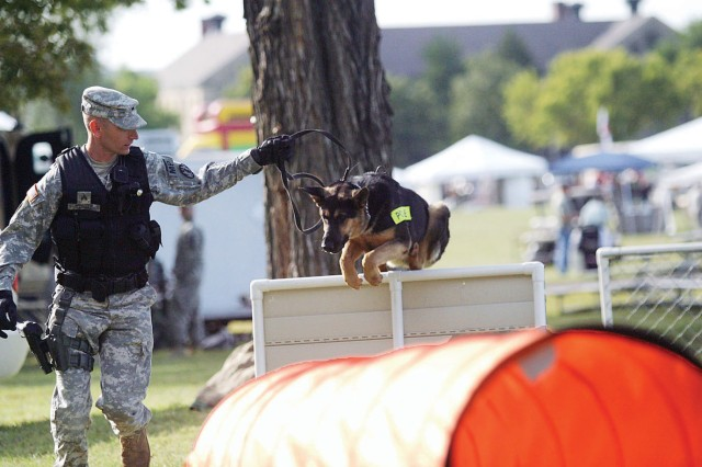 Sgt. Ronald Steudle, HHD, 97th MP Bn., leads Bak, a military working dog, through an obstacle course during a Fall Apple Day Festival demonstration Sept. 24 at Artillery Parade Field, Fort Riley, Kan.
