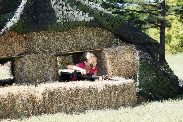 Kristen Stroda, 7, Abilene, Kan., exits a makeshift bunker set up as part of the obstacle course set up in Tuttle Park for Fall Apple Day Festival Sept. 24 at Fort Riley, Kan.
