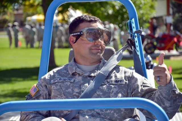 "Spc. Justin Spurgeon, 1st Space Battalion, gives the thumbs up before experiencing a ride on the ""Seat Belt Convincer"" during U.S. Army Space and Missile Defense Command/Army Forces Strategic Command's Safety Expo Day at Peterson Air Force Base's Eagle Park Sept. 22."