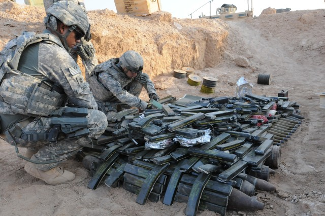 1st Sgt. John R. Cruz (left), first sergeant for the 722nd Explosive Ordnance Disposal Co., supervises the placement of explosives at an ordnance disposal range outside Camp Ramadi, Iraq, Sept. 24. The 722nd detonated over 900 pounds of weapons and munitions, from insurgent and weapons caches, seized by the Iraqi Police. Cruz is a native of Bronx, N.Y.