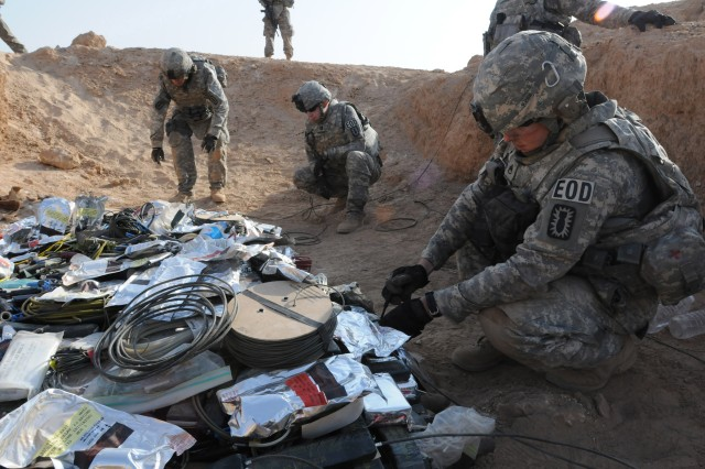 Staff Sgt. James Ward (right), a team sergeant with the 722nd Explosive Ordnance Disposal Co., places a charge in preparation for detonation at an ordnance disposal range outside Camp Ramadi, Iraq, Sept. 24. The 722nd detonated over 900 pounds of weapons and munitions, from insurgent and weapons caches, seized by the Iraqi Police. Ward is a native of Charlotte, N.C.