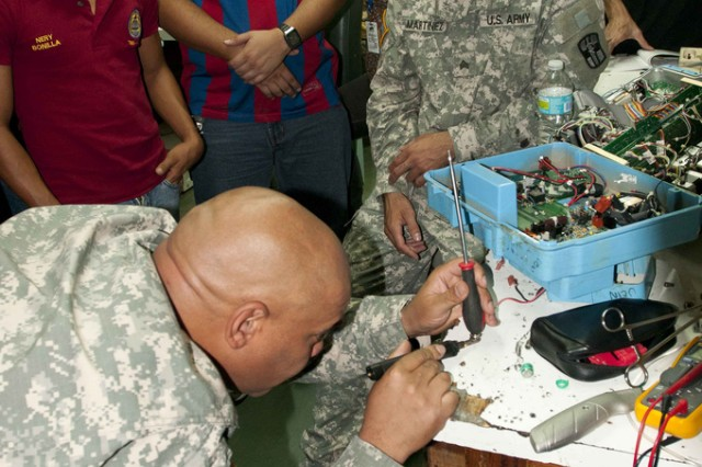 Spc. Robert Gray, of Santa Fe, N.M., shows biomedical technicians from Hospital Escuela in Tegucigalpa, Honduras, how to fuse two batteries together to repair an infusion pump. Grey was part of a three-week mission to the hospital to train their bio-med repairmen and help repair equipment.