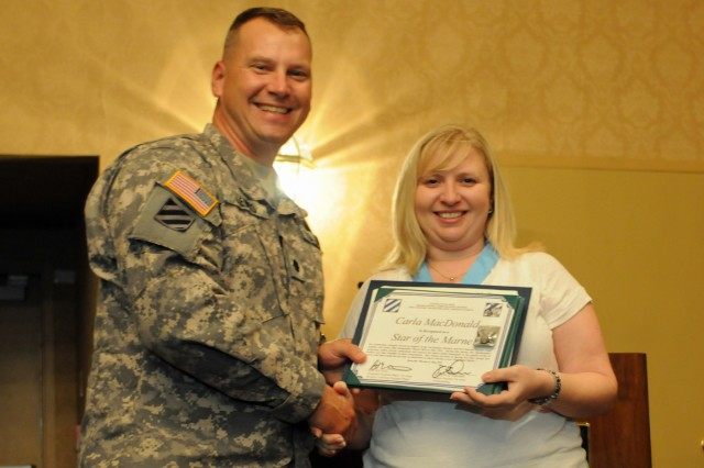 Lieutenant Colonel George E. Lewis III, commander of 4-3 BSTB, 4IBCT, 3rd Inf. Div., presents the Doctor Mary E. Walker Award to Carla MacDonald, the Company A Family Readiness Group leader. A packet was submitted on MacDonald's behalf and was awarded by the boards responsible for granting the Sergeant Audie Murphy Award.