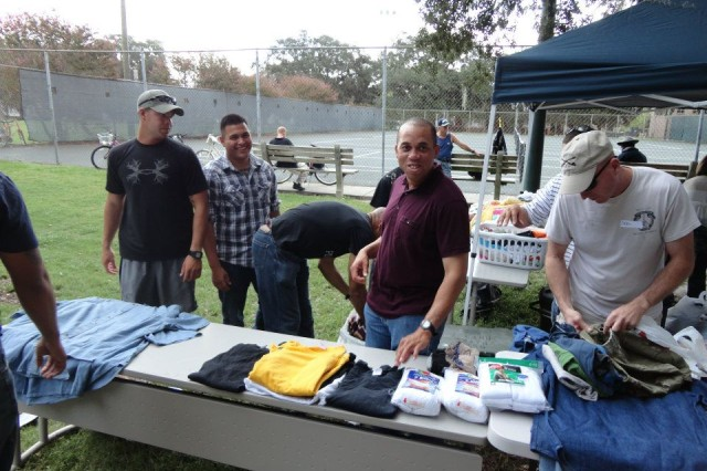 Soldiers and Family members of HHT, 3/7 Cav., lay out clothing and hygiene items at an event in Forsyth Park Savannah for local homeless, Sept 25.