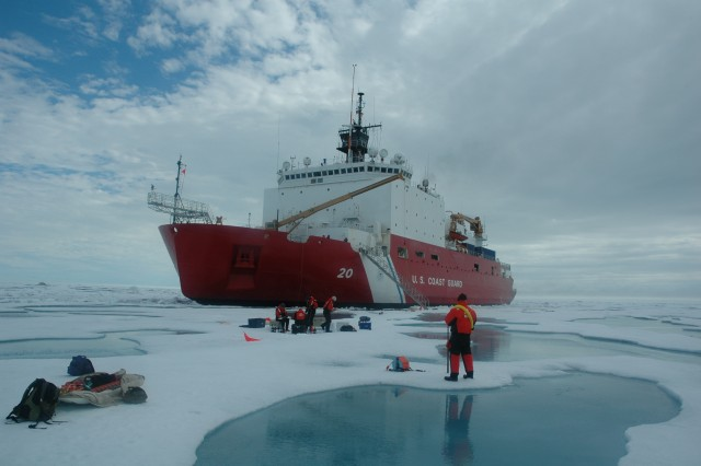 Researchers with the U.S. Army Corps of Engineers and various other insitutions work on the ice of the Chukchi Sea. In the background is the U.S. Coast Guard icebreaker, the Healy. This is a field campaign of the NASA-sponsored ICESCAPE.