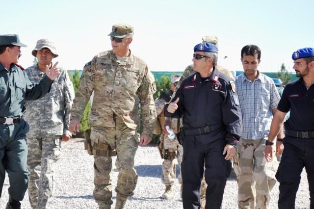 Sgt. Maj. Michael Mosites, DCOM-RS, NTM-A/CSTC-A, listens as Afghan Lt. Col. Shafiqullah Tahiri (left), executive officer of the Adraskan Police Training Center, walks the grounds Sept. 28. (Photo by Jon Connor)