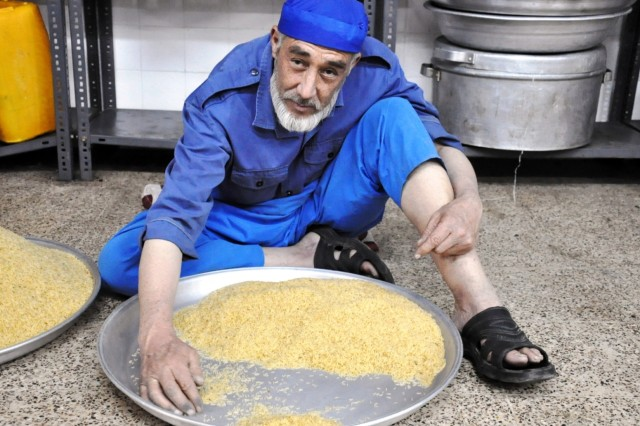 This Afghan employee cleans rice at the Herat Regional Military Hospital Sept. 26. The hospital cares for about 150 outpatients daily. It provides treatment for Afghan forces and family members. (Photo by Jon Connor)