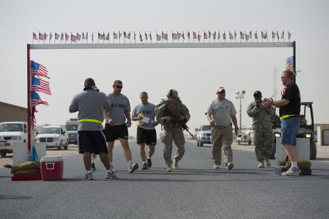 "Staff Sgt. Nicholas A. Kuffel, deployed with 2-135 Infantry, 34th ""Red Bulls"" Infantry Division, completes the Army 10-Miler with full combat load in 2 hours, 53 minutes, 40 seconds at Camp Buehring, Kuwait, Oct. 2, 2011."