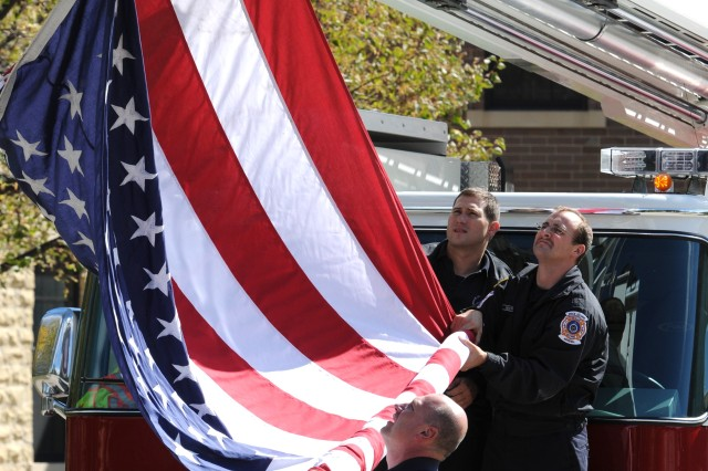 Rock Island Arsenal firefighters unfurl Old Glory in advance of the funeral procession for Army Spc. Chad Dellit, 22, who was buried at the Rock Island (Ill.) National Cemetery Sept. 30. Dellit was a Soldier with the 100th Engineer Co., 30th Engineer Battalion, 20th Engineer Brigade at Fort Bragg, N.C., where he was in training to be a geospatial engineer.