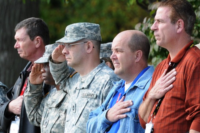 Army Sustainment Command Soldiers and civilian employees line the street in front of the command's headquarters to pay tribute as the funeral procession for Army Spc. Chad Dellit, 22, passes by Sept. 30. Dellit, who was buried at the Rock Island (Ill.) National Cemetery, was a Soldier with the 100th Engineer Co., 30th Engineer Battalion, 20th Engineer Brigade at Fort Bragg, N.C., where he was in training to be a geospatial engineer.