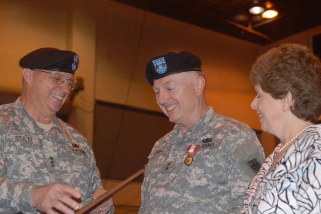 Lt. Gen. Jack C. Stultz, commander of the Army Reserve, hands the certificate that accompanies the Distinguished Service Medal to Maj. Gen. Paul F. Hamm while Hamm's wife Carol looks on during Hamm's retirement ceremony at the Vicksburg Miss., Convention Center April 2, 2011. Hamm received the medal for 37 years of service to the Army from 6 June 1973 to 2 April 2011. (Photo by Maj. Jesse Stalder, 412th TEC Deputy PAO)