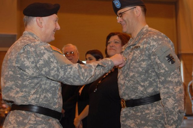 Mrs. Carol Buckler looks on as Maj. Gen. Paul F. Hamm, commander of the 412th Theater Engineer Command, removes the one star Army rank insignia from Brig. Gen. William M. Buckler Jr.'s uniform prior to Buckler's promotion to Major General during a ceremony at the Convention Center in Vicksburg, Miss. Lt. Gen. Jack C. Stultz, commander of the Army Reserve, administered Buckler's promotion, as well as a Change of Command Ceremony where Hamm relinquished command of the 412th TEC to Buckler, and also Hamm's Retirement Ceremony. (Photo by Maj. Jesse Stalder, Deputy Public Affairs Officer, 412th TEC)