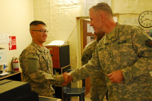 """COS ECHO, Iraq """" Maj. Gen. Thomas Spoehr (right), the Deputy Commanding General for the United States Forces-Iraq, gives a coin to a Post Office Soldier, here, Sept. 03, 2011. The Soldier is part of an efficient team who runs the Post Office on the COS."""