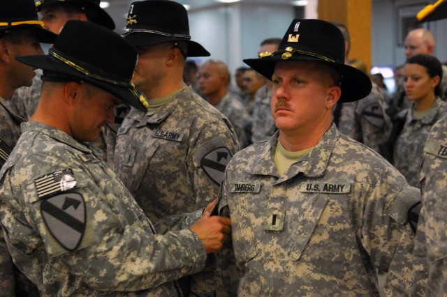 "COS KALSU, Iraq "" Lt. Col. Stephen Dawson, commander of the 1st Brigade Special Troops Battalion, 1st Brigade, 1st Cavalry Division, patches, 1st Lt. Tamberg, here, Sept. 11. The patch ceremony is designed to honor the Soldiers of deployed units, presenting them with a patch to wear on their right sleeve."