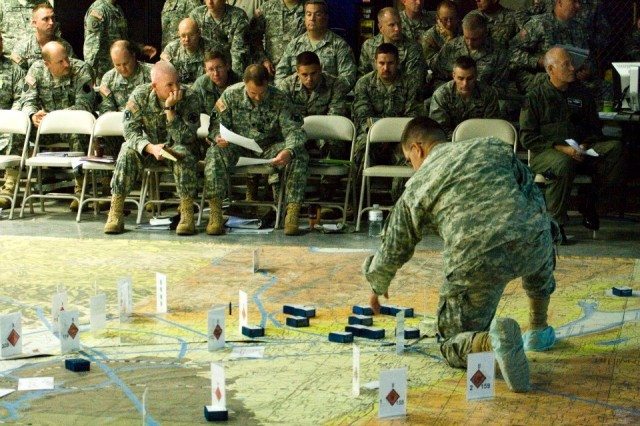 """Markers representing friendly and hostile units are moved in order to illustrate the current situation in the """"map room"""" of Fort Leavenworth's Mission Training Complex as 35th Infantry Division officers look on. The 35th ID (""""Santa Fe Division"""") recently finished a full-spectrum exercise designed to enhance staff skills and provide commanders with mission command experience. (U.S. Army photo provided by the Mission Command Training Program)"""