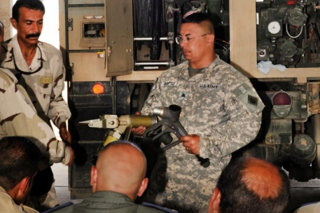 Sgt. Gilbert Britto of Alpha Company, 640th Aviation Support Battalion, shows a class of Iraqi soldiers a fueling nozzle and how it connects to the fueling module on a Heavy Expanded Mobility Tactical Truck at Camp Taji, Iraq, Sept. 13, 2011.