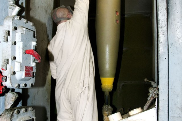 John Brooks, explosive worker, touches up a 500-pound explosive filled bomb at McAlester Army Ammunition Plant.  The bomb body was redesigned to allow venting of gases that could build up pressure and contribute to an explosion.  The plant is the premier bomb provider for the Department of Defense (DOD) and stores one-third of all of DOD's munitions.