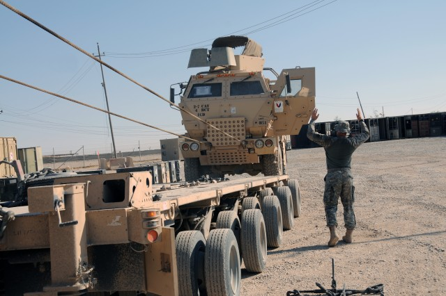 Staff Sgt. Lance Graves, assigned to the 129th Transportation Company out of New Century, Kan., guides a Light Medium Tactical Vehicle onto a trailer of a Heavy Equipment Transport, Sept. 12, 2011, at Forward Operating Base Marez. The 129th are Reserve Soldiers out of New Century, Kan., assigned to assist Joint Task Force Hickory, led by the Tennessee Army National Guard's 230th Sustainment Brigade, to haul equipment out of closing Forward Operating Bases as part of the responsible withdraw of U.S. Forces from Iraq before the Dec. 31, 2011 deadline