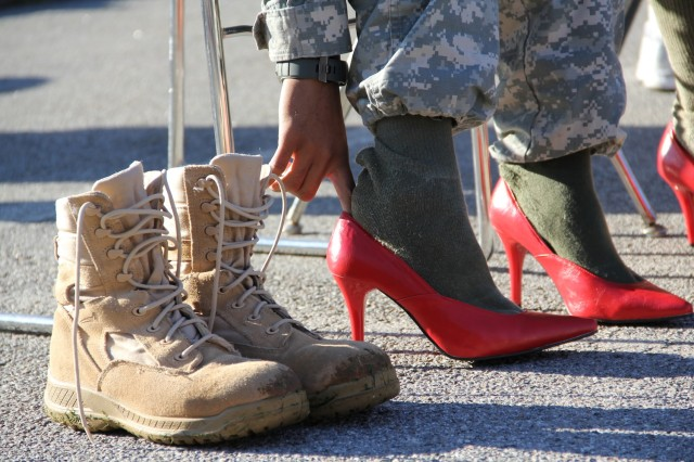 A Soldier swaps his boots for a pair of red high heels during the Walk a Mile in her Shoes event in Vilseck, Germany, Oct. 1, 2011.