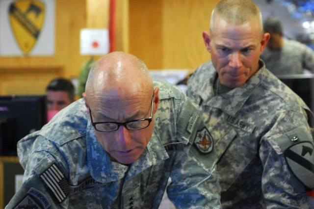 "COS KALSU, Iraq "" Lt. Gen. Frank Helmick (left), the deputy commanding general of operations, United States Forces "" Iraq, looks on as Sgt. Maj. Robert Leimer, the sergeant major of operations for 1st Brigade, 1st Cavalry Division briefs him on current operations, here, Sept. 19."