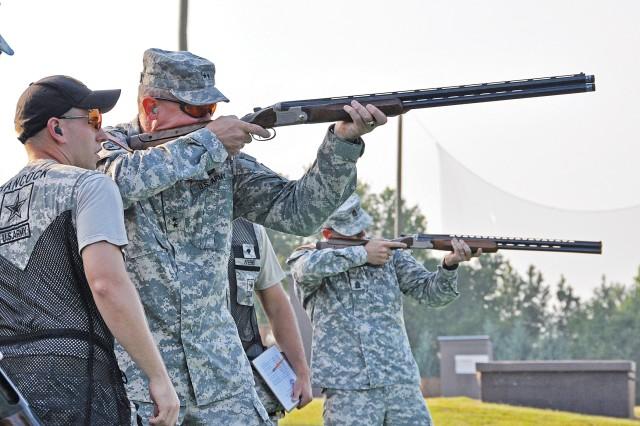 Maj. Gen. Robert Brown, the post commanding general, receives instruction on shotgun shooting from 2008 Olympic gold medalist Sgt. Vincent Hancock, U.S. Army Marksmanship Unit.