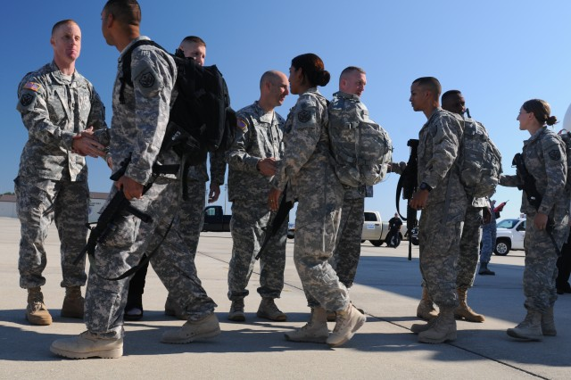 (Right to left) Maj. Gen. Rodney O. Anderson, deputy commanding general; Command Sgt. Maj. Todd Spradling, acting command sergeant major; Lt. Col. Bryan E. Fowler, Headquarters and Headquarters Battalion commander (rear), and other leaders from the XVIII Airborne Corps greet the returning paratroopers from the headquarters' Analysis and Control Element at Green Ramp, Pope Field Oct 5. The ACE group was welcomed back home to Fort Bragg after a year-long deployment in Iraq.