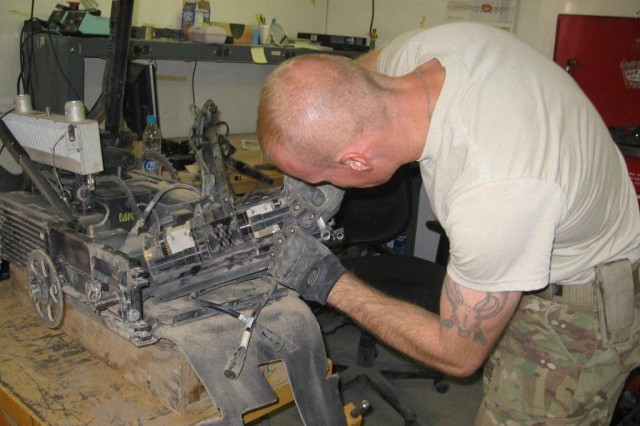 Sgt. First Class Joshua Moon, performs maintenance on one of the many robot systems fielded from their small shop on the 401st Army Field Support Brigade compound on Kandahar Airfield, Afghanistan.