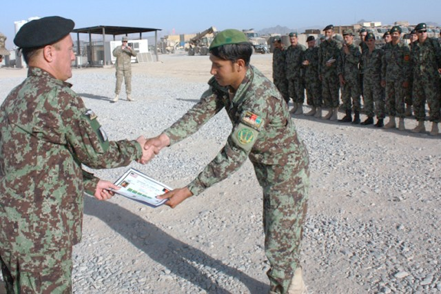 Lt. Col. Hasani, commander of the 4th Kandak, 3rd Brigade, 205th Afghan National Army Corps, presents a student of the ANA NCO Academy with his graduation certificate.