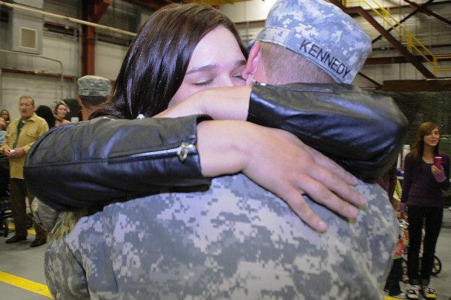 Michelle Kennedy hugs her husband, Chief Warrant Officer 2 Jeffrey Kennedy, during 10th Combat Aviation Brigade's welcome ceremony Oct. 3.