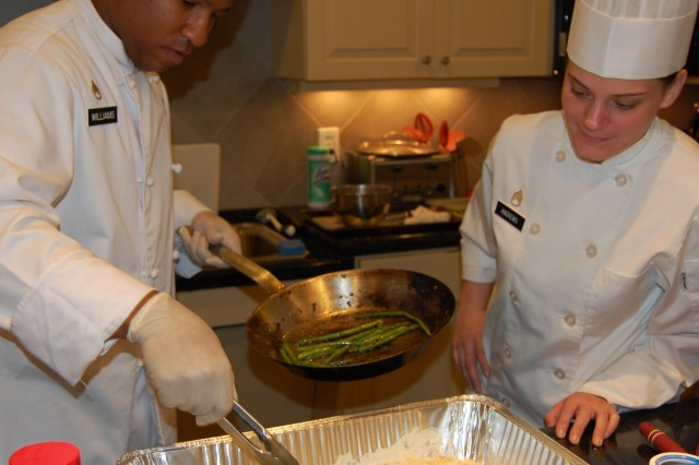 Staff Sgt. Antonio Williams and Staff Sgt. Melinda Andrews put the finishing touches on a fettuccine alfredo and sautéed asparagus dish, prepared for the residents of the Richmond Fisher House. Both Soldiers are students at the Advanced Culinary Course at the Joint Culinary Center of Excellence, Quartermaster School.