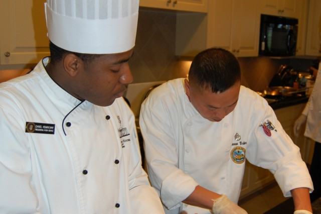 Joint Culinary Center of Excellence instructor, Staff Sergeant Steven Behr (right), takes a moment to show Navy Culinary Specialist 1 Daniel Hemingway proper techniques. Hemingway is one of the Advanced Culinary Course students who volunteered to support a Sept. 24 outreach mission at the Richmond Fisher House.